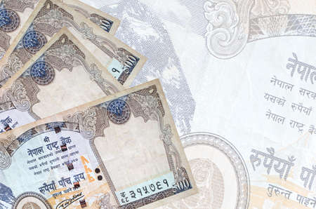 500 Nepalese rupees bills lies in stack on background of big semi-transparent banknote. Abstract business background with copy space