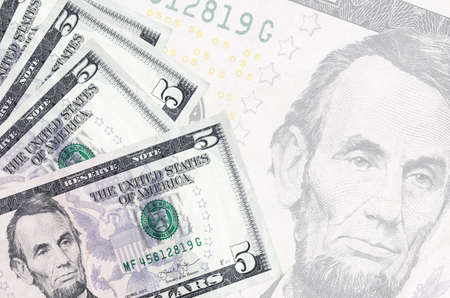 5 US dollars bills lies in stack on background of big semi-transparent banknote. Abstract business background with copy space