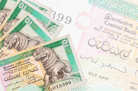 10 Sri Lankan rupees bills lies in stack on background of big semi-transparent banknote. Abstract business background with copy space