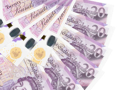 20 British pounds bills lies isolated on white background with copy space stacked in fan shape close up. Financial transactions concept