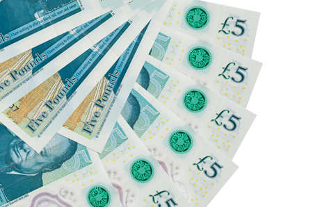 5 British pounds bills lies isolated on white background with copy space stacked in fan shape close up. Financial transactions concept