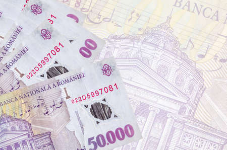 50,000 Romanian leu bills lies in stack on background of big semi-transparent banknote. Abstract business background with copy space