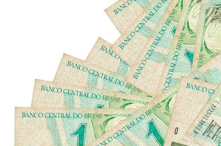 1 Brazilian real bills lies in different order isolated on white. Local banking or money making concept. Business background banner Фото со стока