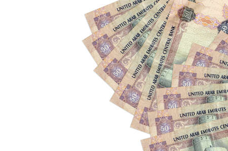 50 UAE dirhams bills lies isolated on white background with copy space. Rich life conceptual background. Big amount of national currency wealth