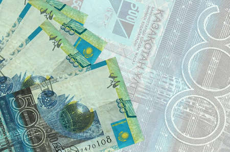 500 Kazakhstani tenge bills lies in stack on background of big semi-transparent banknote. Abstract business background with copy space