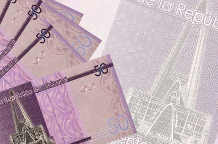 50 Dominican pesos bills lies in stack on background of big semi-transparent banknote. Abstract business background with copy space