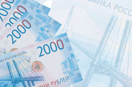 2000 russian rubles bills lies in stack on background of big semi-transparent banknote. Abstract business background with copy space