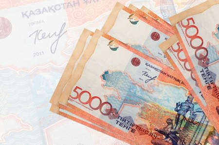 5000 Kazakhstani tenge bills lies in stack on background of big semi-transparent banknote. Abstract presentation of national currency. Business concept