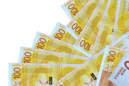 100 Israeli new shekels bills lies in different order isolated on white. Local banking or money making concept. Business background banner Фото со стока