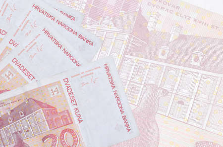 20 Croatian kuna bills lies in stack on background of big semi-transparent banknote. Abstract business background with copy space