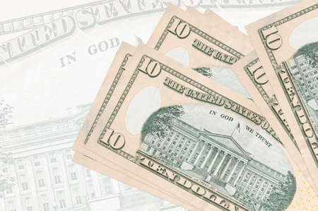 10 US dollars bills lies in stack on background of big semi-transparent banknote. Abstract presentation of national currency. Business concept