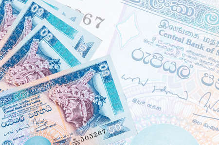 50 Sri Lankan rupees bills lies in stack on background of big semi-transparent banknote. Abstract business background with copy space