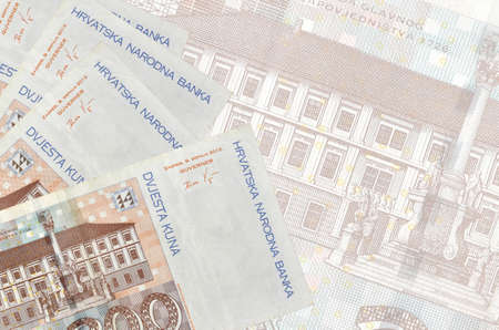 200 Croatian kuna bills lies in stack on background of big semi-transparent banknote. Abstract business background with copy space Фото со стока