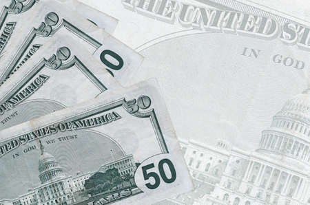 50 US dollars bills lies in stack on background of big semi-transparent banknote. Abstract business background with copy space Фото со стока