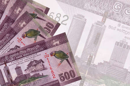 500 Sri Lankan rupees bills lies in stack on background of big semi-transparent banknote. Abstract business background with copy space