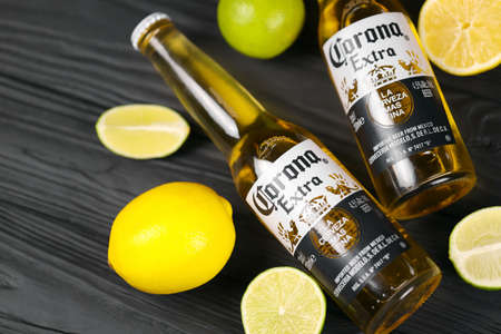 KHARKOV, UKRAINE - DECEMBER 9, 2020: Bottles of Corona Extra Beer with lime slices. Corona produced by Grupo Modelo with Anheuser Busch InBev is the most popular imported beer in the US