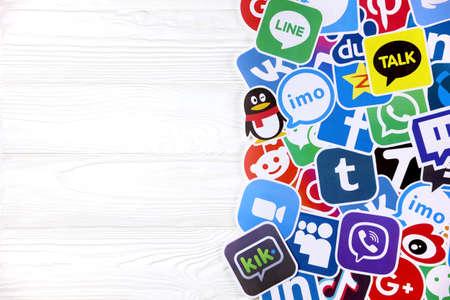 KHARKOV, UKRAINE - DECEMBER 26, 2020: Paper of most popular social networks and mobile messengers on wooden background. Facebook instagram youtube twitter tiktok twitch reddit and others