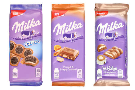 KHARKOV, UKRAINE - DECEMBER 8, 2020: Purple Milka chocolate bars on white background. Milka is a Swiss brand of chocolate confection manufactured internationally by company Mondelez International Редакционное