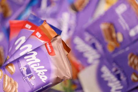 KHARKOV, UKRAINE - DECEMBER 8, 2020: Many wrappings of purple Milka chocolate. Milka is a Swiss brand of chocolate confection manufactured internationally by company Mondelez International