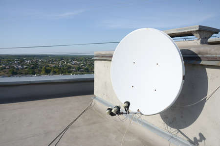 White satellite dish with three converters mounted on residental building rooftop concrete wall. Satellite television advertisement