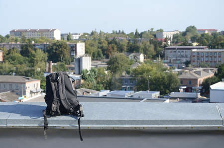 Black backpack lies on metal border of residental multistorey building rooftop in sunny weather outdoors