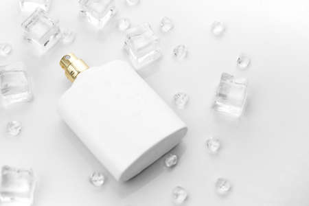 Female perfume mat white bottle, objective photograph of perfume bottle in ice cubes and water on white table. View from above. Mockup product photo, concept of freshness and aroma