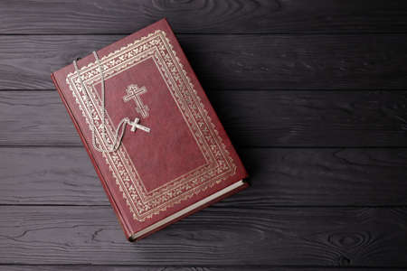Silver necklace with crucifix cross on christian holy bible book on black wooden table. Asking blessings from God with the power of holiness, which brings luck and shows forgiveness.