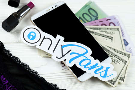 KHARKOV, UKRAINE - FEBRUARY 14, 2021: Onlyfans paper logo with dollar bills, red lipstick with smartphone and black lingerie on white wooden table. OnlyFans is content subscription service