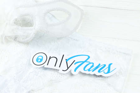 KHARKOV, UKRAINE - FEBRUARY 14, 2021: Onlyfans paper logo and white lingerie with carnival mask on white table. OnlyFans is content subscription service based in London, United Kingdom Redakční