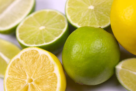 Many halves and slices of yellow lemon and green lime on light white table. Fresh fruits on kitchen top