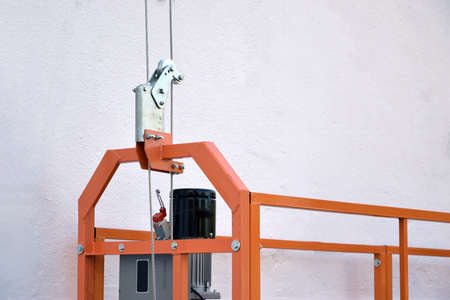 Hoist supply and safety lock as part of suspended wire rope platform for facade works on high multistorey buildings. Hoist for elevation, raising or lifting cradle platform