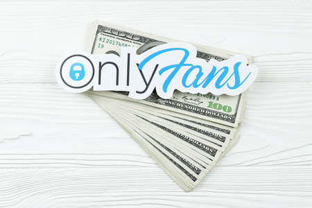 KHARKOV, UKRAINE - FEBRUARY 14, 2021: Onlyfans paper logo with dollar bills on white wooden table. OnlyFans is content subscription service based in London, United Kingdom