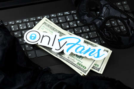 KHARKOV, UKRAINE - FEBRUARY 14, 2021: Onlyfans paper logo with smartphone and dollar bills on black laptop keyboard. OnlyFans is content subscription service based in London, United Kingdom