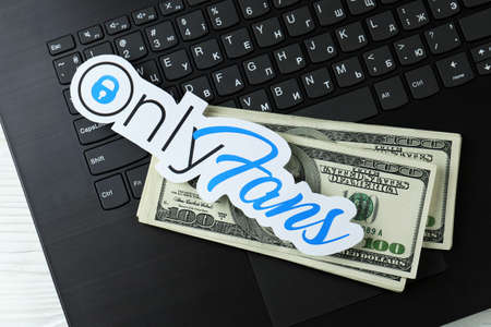 KHARKOV, UKRAINE - FEBRUARY 14, 2021: Onlyfans paper logo and dollar bills on black laptop keyboard. OnlyFans is content subscription service based in London, United Kingdom