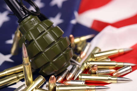 F1 frag grenade and many yellow bullets and cartridges on United States flag. Concept of gun trafficking on USA territory or special operations