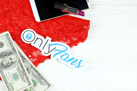KHARKOV, UKRAINE - FEBRUARY 14, 2021: Onlyfans paper logo with dollar bills, red lipstick with smartphone and red lingerie on white wooden table. OnlyFans is content subscription service Editorial