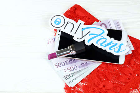 KHARKOV, UKRAINE - FEBRUARY 14, 2021: Onlyfans paper logo with euro bills, red lipstick with smartphone and red lingerie on white wooden table. OnlyFans is content subscription service