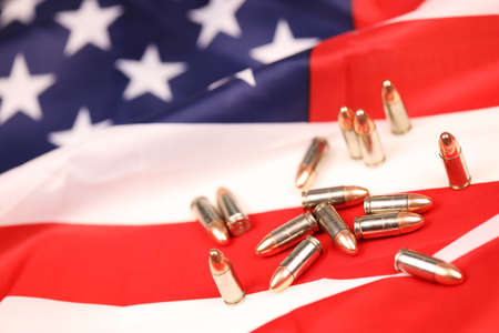 Many yellow 9mm bullets and cartridges on United States flag. Concept of gun trafficking on USA territory or special operations