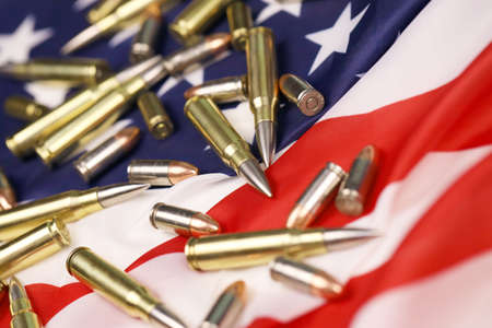 Many yellow 9mm and 5.56mm bullets and cartridges on United States flag. Concept of gun trafficking on USA territory or special operations