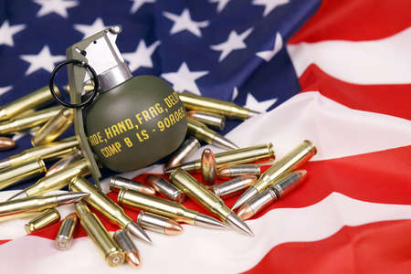 M67 frag grenade and many yellow bullets and cartridges on United States flag. Concept of gun trafficking on USA territory or special operations