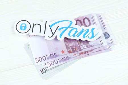 KHARKOV, UKRAINE - FEBRUARY 14, 2021: Onlyfans paper logo with euro bills on white wooden table. OnlyFans is content subscription service based in London, United Kingdom Redakční