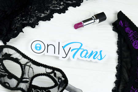 KHARKOV, UKRAINE - FEBRUARY 14, 2021: Onlyfans paper logo, red lipstick with carnival mask and black lingerie on white wooden table. OnlyFans is content subscription service