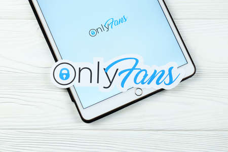 KHARKOV, UKRAINE - FEBRUARY 14, 2021: Onlyfans paper logo with website on iPad screen on white wooden table. OnlyFans is content subscription service based in London, United Kingdom Redakční