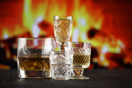 Different alcohol drinks in glass on wooden surface on fireplace background. Luxury elite alcohol in glass cups. Low key dark scene