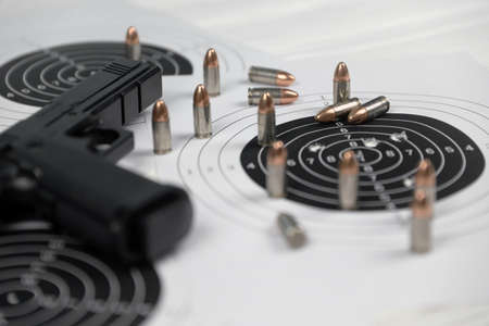 Gun and many bullets shooting targets on white table in shooting range polygon. Training for aiming and shooting accuracy