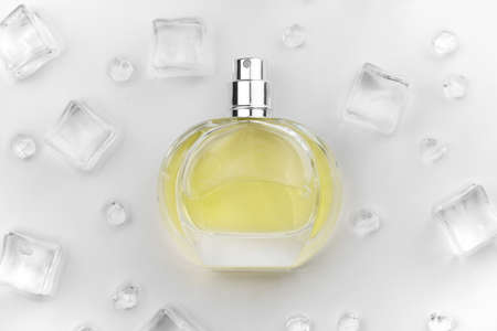 Female perfume yellow bottle, Objective photograph of perfume bottle in ice cubes and water on white table. View from above. Mockup product photo, concept of freshness and aroma Reklamní fotografie