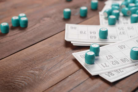 Many barrels with numbers and cards for lotto or russian bingo table game on wooden surface. Russian lotto has similar rules to classical worldwide bingo game