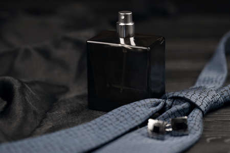 A bottle of mens cologne and cufflinks with blue tie lie on a black luxury fabric background on a wooden table. Mens classic accessories. Shallow DOF Reklamní fotografie