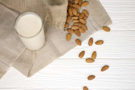 Glass of almond milk with almond nuts on canvas fabric on white wooden table. Dairy alternative milk for detox, healthy eating and diets. Selective focus