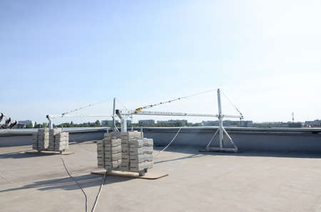 Counter weight or weight balance concrete blocks or bricks as part of suspended wire rope platform for facade works on high multistorey buildings. Many blocks with metal transportation handles